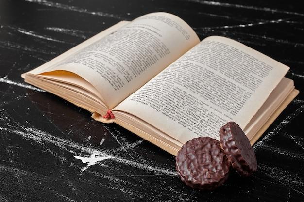 Cookies de chocolate com um livro antigo à parte.