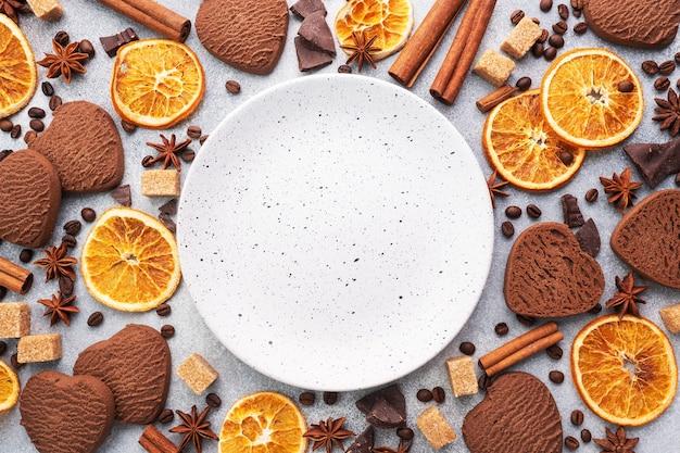 Cookies de chocolate coração, laranjas, canela e especiarias picantes em uma mesa cinza, vista superior, copie o espaço.