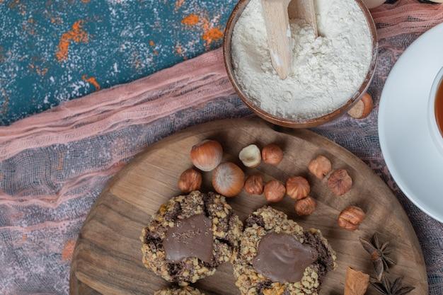 Cookies de chocolate crocante com nozes em uma placa de madeira.