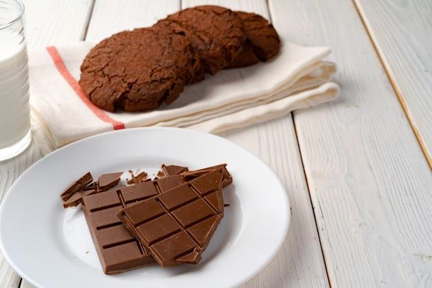 Cookies de chocolate e barra de chocolate na placa de madeira branca
