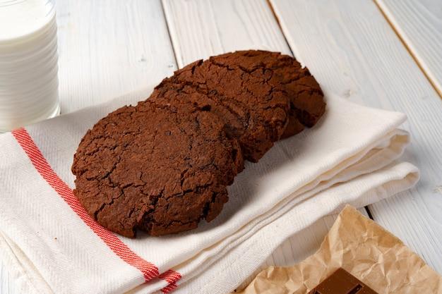 Cookies de chocolate e barra de chocolate quebrada na placa de madeira branca