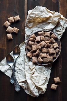 Cookies de chocolate e colheres em fundo de madeira