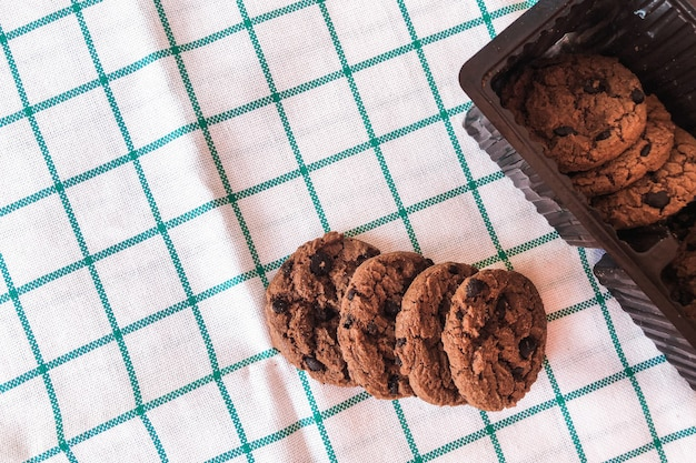 Cookies de chocolate em embalagens em fundo de pano.