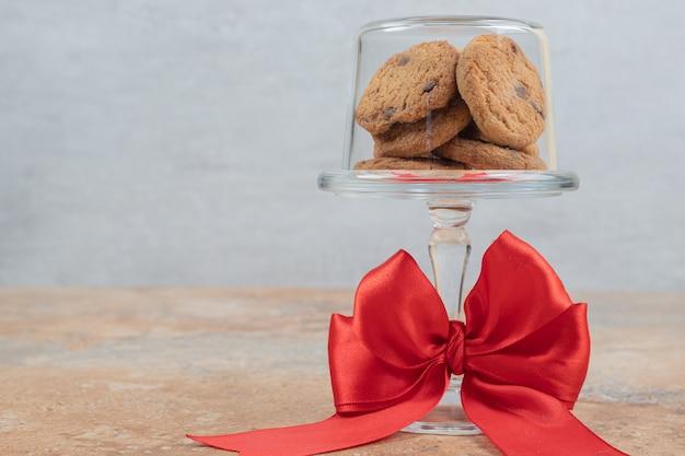 Cookies de chocolate em placa de vidro amarrada com fita.