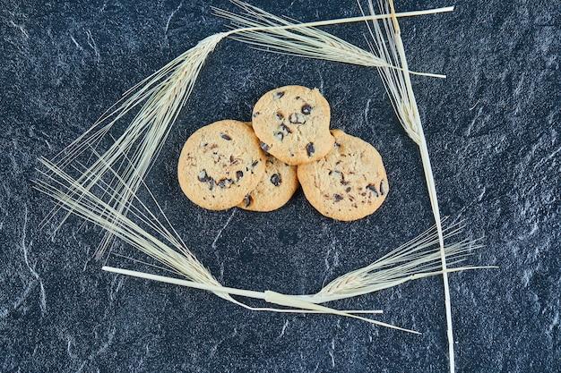 Cookies de chocolate em uma superfície de mármore com espigas de trigo