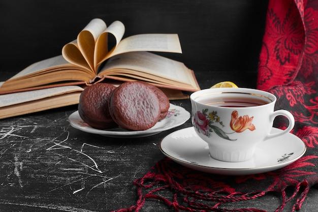 Cookies de chocolate em uma xícara de madeira com uma xícara de chá.