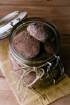 Cookies de chocolate no papel em jarra de vidro