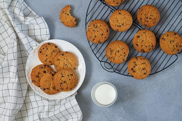 Cookies de chocolate recém-assados e copo de leite na vista de cima da mesa de pedra