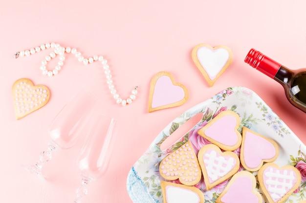 Cookies de coração, taças de vinho e vinho em rosa pastel