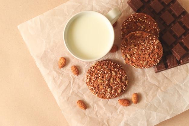 Cookies de farinha de aveia caseiros saborosos em uma placa com porcas, copo do leite em um fundo brilhante, vista superior.