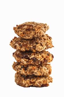 Cookies de farinha de aveia do vegetariano com datas e uma banana isolada no fundo branco.