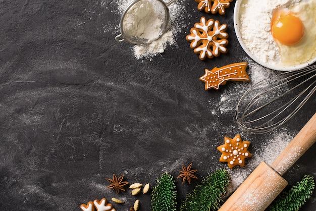 Cookies de fundo de pão de mel de natal com ingredientes para cozinhar, conceito de feriado de ano novo feliz na textura escura, espaço de cópia