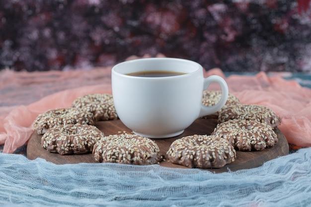 Cookies de gergelim de cacau em uma placa de madeira com uma xícara de chá.