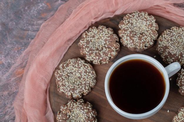 Cookies de gergelim de cacau isolados na placa de madeira com um copo de bebida.