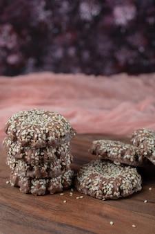 Cookies de gergelim de cacau isolados na placa de madeira.