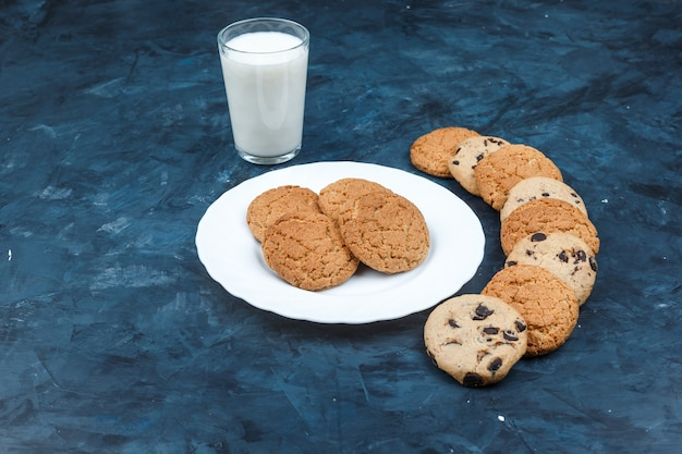 Cookies de manteiga de amendoim de vista de alto ângulo em chapa branca com leite, diferentes tipos de cookies em fundo azul escuro. horizontal