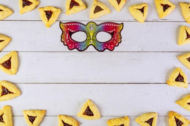 Cookies de máscara e triângulo de purim em fundo branco.
