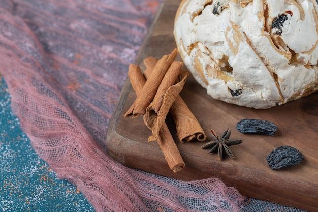 Cookies de merengue branco com passas pretas em uma placa de madeira.