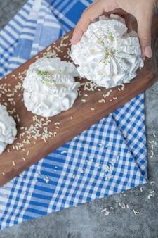 Cookies de merengue branco com pó de coco em uma placa de madeira na toalha azul.
