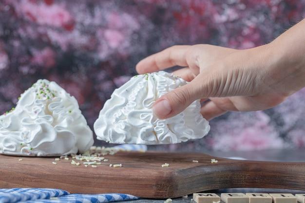 Cookies de merengue branco em uma placa de madeira com pó de coco na parte superior.