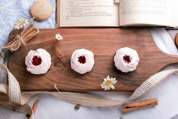 Cookies de merengue com geléia de morango e um livro à parte.