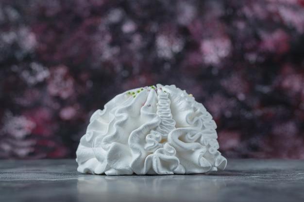 Cookies de merengue floral branco em cima da mesa.
