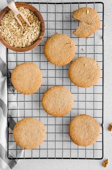 Cookies de passa de aveia recentemente cozidas na cremalheira de refrigeração em uma pedra clara. close up de cima com iluminação direcional natural. orientação vertical.