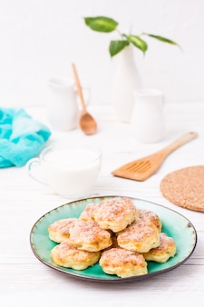 Cookies de queijo cottage polvilhadas com açúcar em um prato e um copo de leite em uma mesa de madeira