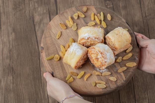 Cookies de rolo frito com passas brancas e recheios doces em uma placa de madeira.