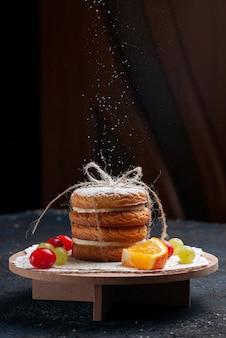 Cookies de sanduíche deliciosos de vista frontal amarrados gostosos com frutas fatiadas recebendo açúcar em pó no bolo de mesa azul escuro
