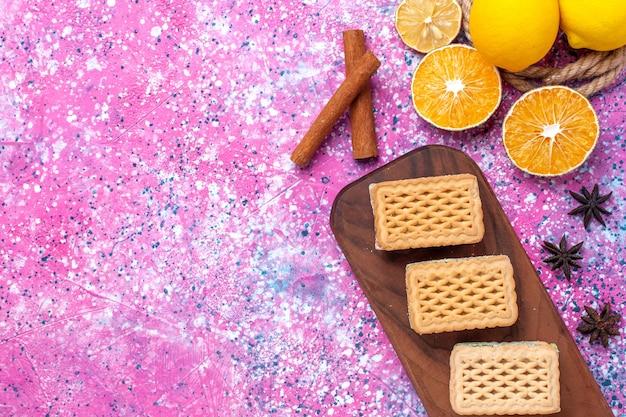 Cookies de sanduíche waffle de vista de cima de perto com recheio de creme de frutas e chá na mesa rosa claro.