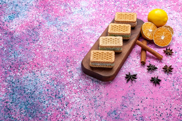 Cookies de sanduíche waffle de vista frontal com recheio de creme de frutas na mesa rosa claro.