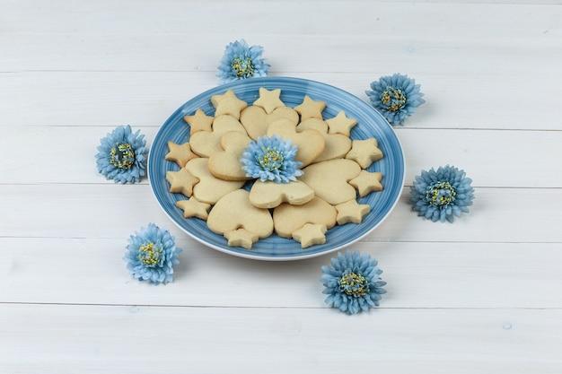 Cookies de vista de alto ângulo em prato com flores sobre fundo de madeira. horizontal