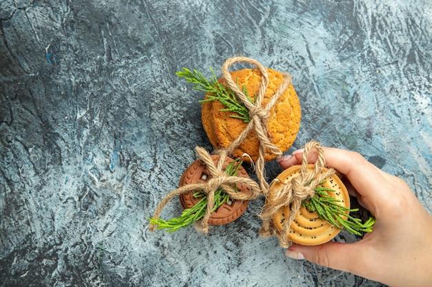 Cookies de vista de cima amarrados com cordas de biscoitos em mãos femininas no espaço livre de superfície cinza