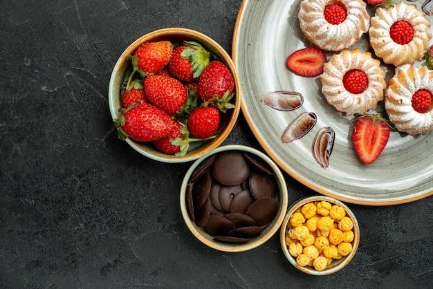 Cookies de vista de cima em close-up com tigelas de morango com chocolate, morango e noz-castanha ao lado de biscoitos apetitosos no lado direito da mesa escura