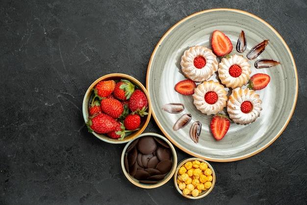 Cookies de vista de cima em close-up com tigelas de morango com chocolate, morango e nozes, ao lado de biscoitos apetitosos com chocolate e morango na superfície preta