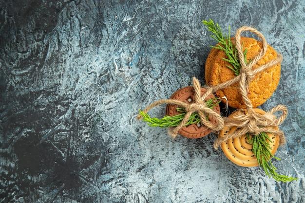 Cookies de vista superior amarrados com cordas e folhas de pinheiro na superfície cinza