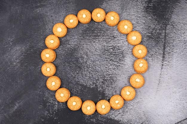 Cookies de vista superior, dispostas em círculo na superfície escura