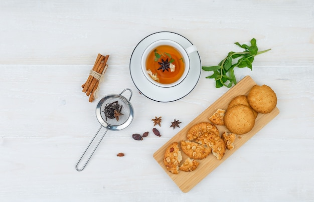 Cookies de vista superior na tábua de corte com chá de ervas, coador de chá e especiarias na superfície branca