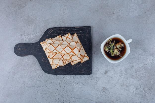 Cookies de waffle espalhados com uma xícara de chá de ervas.