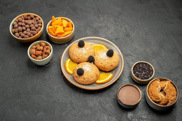 Cookies deliciosos de cima com batatas fritas e nozes em uma superfície cinza-escura biscoito biscoito chá doce bolo
