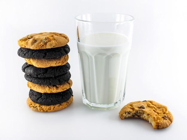 Cookies diversos e um copo de leite em um branco.