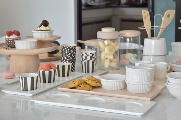 Cookies e cupcakes com configuração de bakeware bonito na tabela superior branca