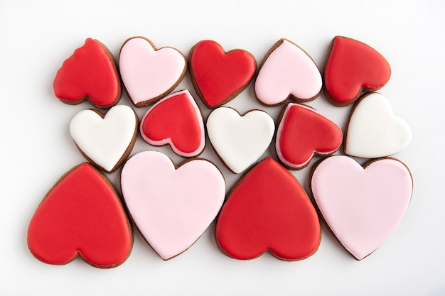 Cookies em forma de coração com glacê de açúcar vermelho, rosa e branco. fundo de corações. deleite do dia dos namorados.