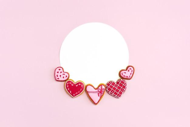 Cookies em forma de coração plana leigos em rosa com maquete redonda para o dia dos namorados.