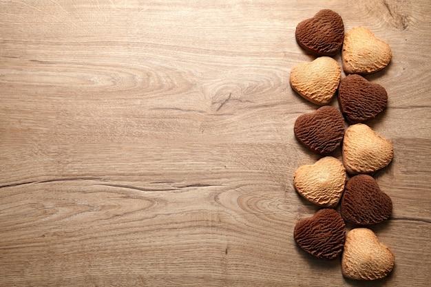 Cookies em fundo de madeira em forma de coração. manteiga cozida e biscoitos de chocolate, espaço vazio para o texto. dia dos namorados