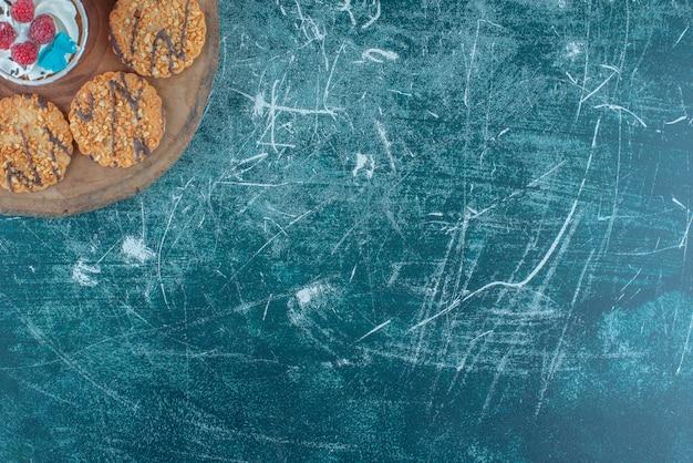 Cookies em torno de um bolinho em uma placa de madeira sobre fundo azul. foto de alta qualidade