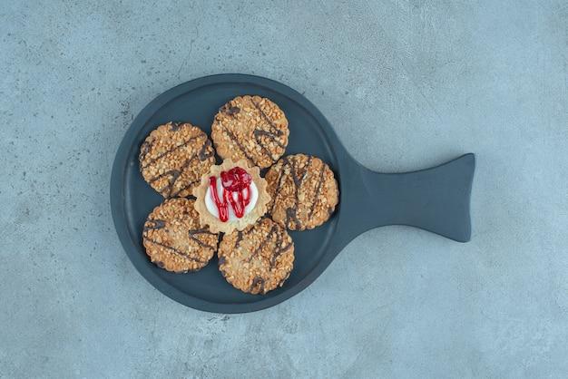 Cookies em torno de um cupcake em uma pequena assadeira sobre superfície de mármore