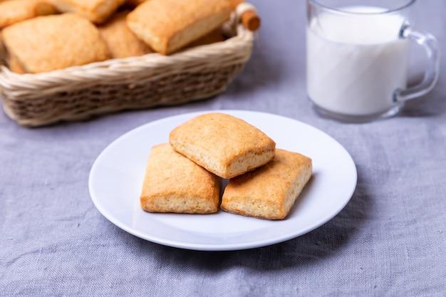 Cookies em um prato branco. uma cesta de biscoitos e um copo de leite. fechar-se.