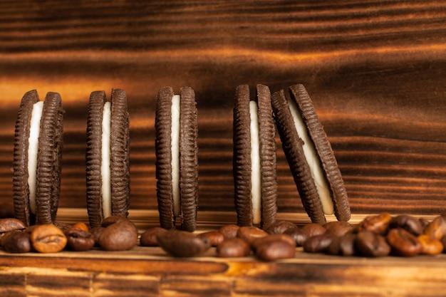 Cookies em uma mesa marrom de uma árvore queimada com grãos de café espalhados na mesa.